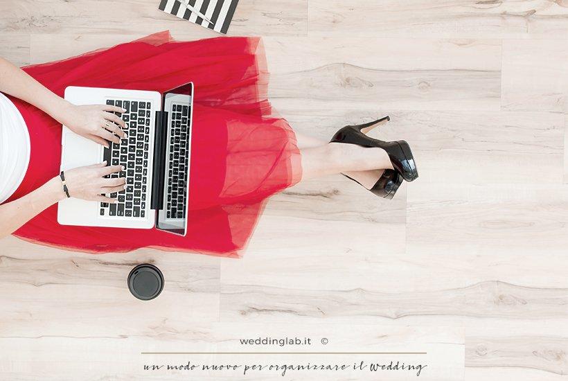 ragazza seduta col vestito in tulle rosso, scarpe col tacco nere naviga sul macbook alla ricerca di un regalo per lui