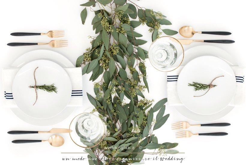 tavola apparecchiata per due con centrotavola di eucalipto verde e posate color oro