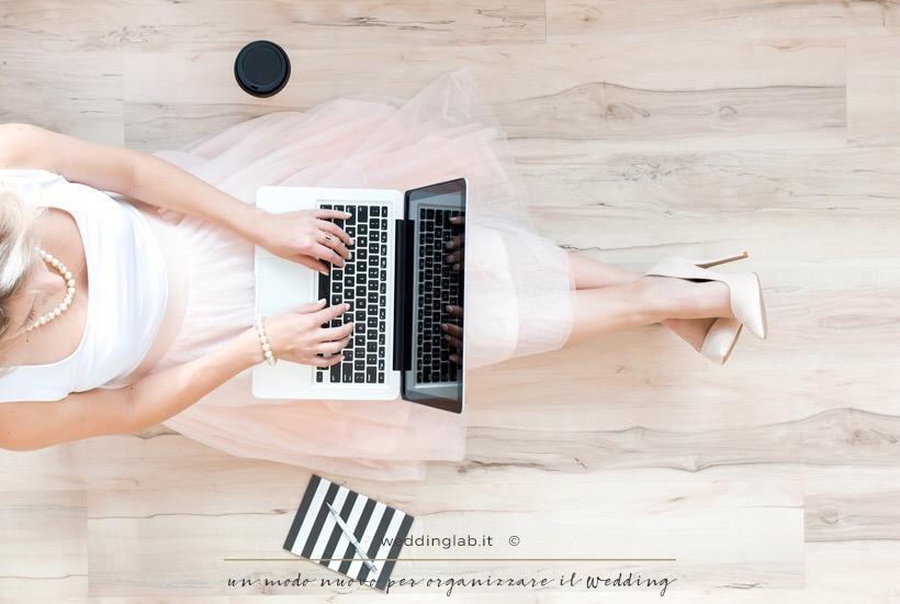 ragazza seduta col vestito in tulle rosa, scarpe col tacco rosa e con macbook e caffè